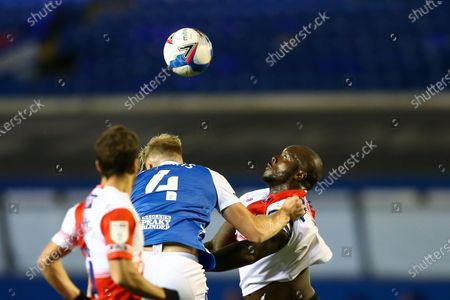 Marc Roberts (4) of Birmingham City and Adebayo Akinfenwa (20) of Wycombe Wanderers compete for the aerial ball
