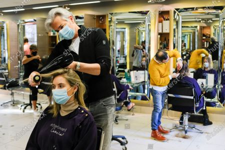 Richard Ward, owner of Richard Ward Hair & MetroSpa wears a protective face mask as he works in his salon in London, . Britain is preparing to join large swathes of Europe in a coronavirus lockdown designed to save its health care system from being overwhelmed. Pubs, along with restaurants, hairdressers and shops selling non-essential items will have to close Thursday until at least Dec. 2