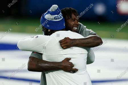 Stock Image of Tampa Bay Buccaneers linebacker Jason Pierre-Paul (90) embraces New York Giants defensive tackle Dalvin Tomlinson (94) before an NFL football game, in East Rutherford, N.J