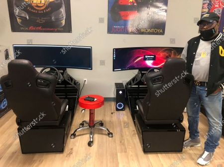 Urban Youth Racing School founder Anthony Martin poses for a photo with racing simulators donated by former NASCAR driver Kyle Larson, in Philadelphia. The school has made it its mission to introduce inner-city youngsters, most of them black, to the motorsports world