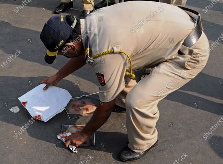 Stock Picture of A policeman picks up posters of an Indian National Congress politician Rahul Gandhi during the demonstration. Supporters of Bharatiya Janata Party (BJP) protested against the arrest of editor-in-chief of Republic TV, Arnab Goswami for allegedly abetting suicide of an architect and interior designer Anvay Naik and his mother.