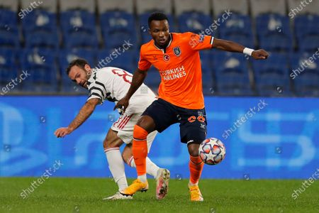 Manchester United's Juan Mata, left, fights for the ball with Basaksehir's Boli Bolingoli-Mbombo during the Champions League group H soccer match between Istanbul Basaksehir and Manchester United at the Fatih Terim stadium in Istanbul