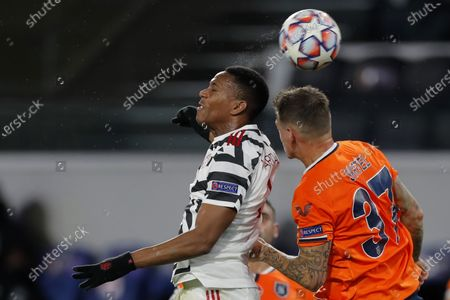 Manchester United's Anthony Martial, left, jumps for the ball with Basaksehir's Martin Skrtel during the Champions League group H soccer match between Istanbul Basaksehir and Manchester United at the Fatih Terim stadium in Istanbul