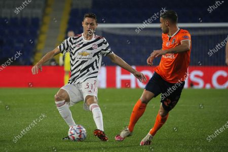 Manchester United's Nemanja Matic, left, is challenged by Basaksehir's Aziz Behich during the Champions League group H soccer match between Istanbul Basaksehir and Manchester United at the Fatih Terim stadium in Istanbul