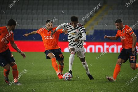 Manchester United's Marcus Rashford, second right, is challenged by Basaksehir's Berkay Ozcan, second left, Basaksehir's Aziz Behich, right, and Basaksehir's Rafael during the Champions League group H soccer match between Istanbul Basaksehir and Manchester United at the Fatih Terim stadium in Istanbul