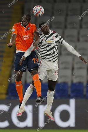 Basaksehir's Demba Ba, left, jumps for the ball with with Manchester United's Axel Tuanzebe during the Champions League group H soccer match between Istanbul Basaksehir and Manchester United at the Fatih Terim stadium in Istanbul