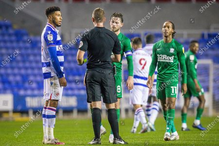 Referee John Brooks speaks with Reading forward Lucas João (18) and Preston North End midfielder Alan Browne (8) following a pitch brawl, fight, during the EFL Sky Bet Championship match between Reading and Preston North End at the Madejski Stadium, Reading