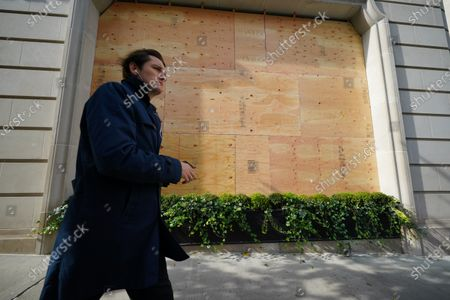 A person passing by a boarded-up Ralph Lauren Store along Madison Avenue in New York City.