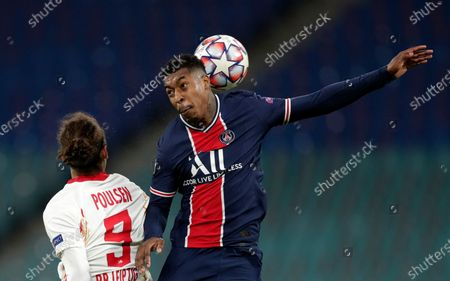 PSG's Presnel Kimpembe, right, duels for the ball with Leipzig's Yussuf Poulsen during the Champions League group H soccer match between RB Leipzig and Paris Saint Germain at the RB Arena in Leipzig, Germany