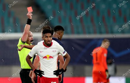 Referee Szymon Marciniak shows a red card to PSG's Presnel Kimpembe during the Champions League group H soccer match between RB Leipzig and Paris Saint Germain at the RB Arena in Leipzig, Germany