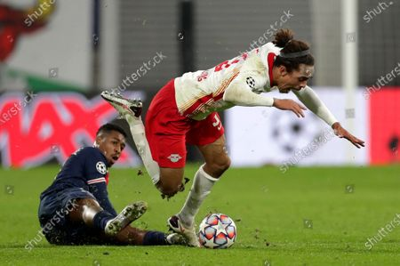 PSG's Presnel Kimpembe, left, duels for the ball with Leipzig's Yussuf Poulsen during the Champions League group H soccer match between RB Leipzig and Paris Saint Germain at the RB Arena in Leipzig, Germany