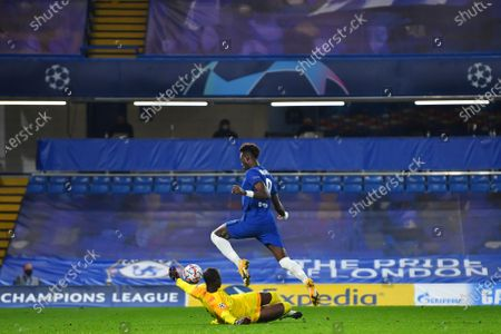 Chelsea's Tammy Abraham jumps over Rennes' goalkeeper Alfred Gomis during a Group E Champions League soccer match between Chelsea and Rennes at Stamford Bridge stadium in London, England