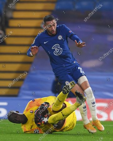 Rennes' goalkeeper Alfred Gomis saves at the feet of Chelsea's Hakim Ziyech during a Group E Champions League soccer match between Chelsea and Rennes at Stamford Bridge stadium in London, England