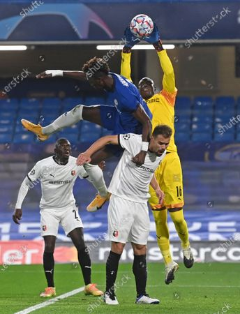 Rennes' goalkeeper Alfred Gomis catches the ball as Chelsea's Tammy Abraham jumps to challenge during a Group E Champions League soccer match between Chelsea and Rennes at Stamford Bridge stadium in London, England