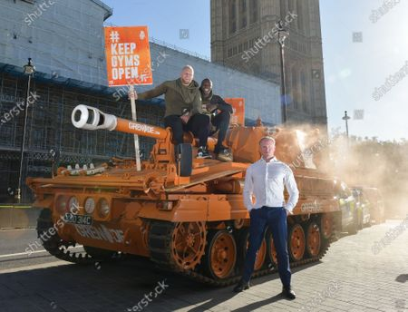 Pictured: James Haskell and Paul Olima stand ontop of the Grenade® tank outside the Houses of Parliament with Ilford South MP Sam Tarry in protest of #KeepingGymsOpen during the second Coronavirus lockdown that starts tomorrow in England.  A bright orange tank driven by England rugby star James Haskell headed to Parliament Square today and caused a ruckus as it was stopped by police. The former international was joining performance nutrition brand Grenade in protesting gyms and leisure centres being classified as 'non-essential' under new lockdown regulations.  There were a reported 22 million visits to gyms after they reopened in July, with just 78 Covid cases being tracked to these locations. With England set to return to a nationwide lockdown from tomorrow (Thursday November 4) these leisure facilities will once again be forced to close, not being classed as 'essential'.