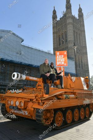Pictured: James Haskell and Paul Olima stand ontop of the Grenade® tank outside the Houses of Parliament in protest of #KeepingGymsOpen during the second Coronavirus lockdown that starts tomorrow in England.  A bright orange tank driven by England rugby star James Haskell headed to Parliament Square today and caused a ruckus as it was stopped by police. The former international was joining performance nutrition brand Grenade in protesting gyms and leisure centres being classified as 'non-essential' under new lockdown regulations.  There were a reported 22 million visits to gyms after they reopened in July, with just 78 Covid cases being tracked to these locations. With England set to return to a nationwide lockdown from tomorrow (Thursday November 4) these leisure facilities will once again be forced to close, not being classed as 'essential'.