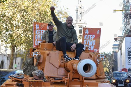 Pictured: Pedestrians look on as James Haskell rides ontop of the Grenade® tank around Central London in protest of #KeepingGymsOpen during the second Coronavirus lockdown that starts tomorrow in England.  A bright orange tank driven by England rugby star James Haskell headed to Parliament Square today and caused a ruckus as it was stopped by police. The former international was joining performance nutrition brand Grenade in protesting gyms and leisure centres being classified as 'non-essential' under new lockdown regulations.  There were a reported 22 million visits to gyms after they reopened in July, with just 78 Covid cases being tracked to these locations. With England set to return to a nationwide lockdown from tomorrow (Thursday November 4) these leisure facilities will once again be forced to close, not being classed as 'essential'.