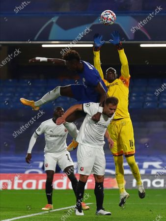 Rennes' goalkeeper Alfred Gomis, right, makes a save during the Champions League Group E soccer match between Chelsea and Rennes at Stamford Bridge, London, England