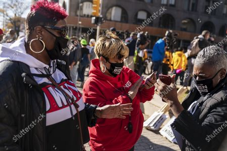 Dorothy Hawkins, from left, Nia Winston and Zinnia Patcas, supporters of Democratic presidential candidate former Vice President Joe Biden, look on their phones as news breaks that Wisconsin is called for Biden during a rally calling for very cote to be counted near the Detroit Department of Elections building in Detroit, Mich