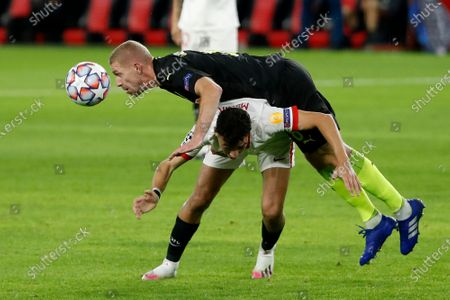 Krasnodar's Yury Gazinsky falls on top of Sevilla's Munir El Haddadi during the Champions League group E soccer match between Sevilla FC and FC Krasnodar, at the Ramon Sanchez Pizjuan stadium in Seville, Spain