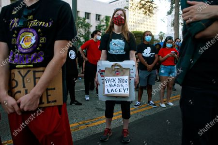 Meghan Magno of Los Angeles holds a Pack Your Bag Lacey sign at the BLM LA Jackie Lacey will go celebration in front of the Hall of Justice on Wednesday, Nov. 4, 2020 in Los Angeles, CA. (Jason Armond / Los Angeles Times)