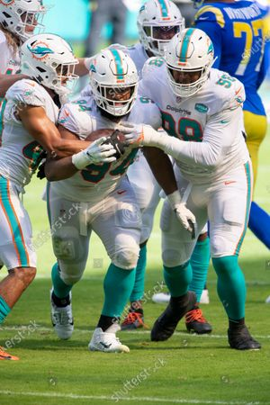 Miami Dolphins defensive tackle Christian Wilkins (94) intercepts a pass from Los Angeles Rams quarterback Jared Goff (not shown) and celebrates with Miami Dolphins cornerback Nik Needham (40) and Miami Dolphins defensive tackle Raekwon Davis (98) during an NFL football game, in Miami Gardens, Fla