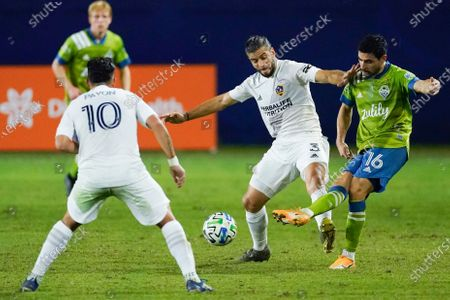 Seattle Sounders midfielder Alex Roldan, right, makes a pass next to LA Galaxy defender Emiliano Insua, center, and forward Cristian Pavon, left, during the first half of an MLS soccer match, in Carson, Calif