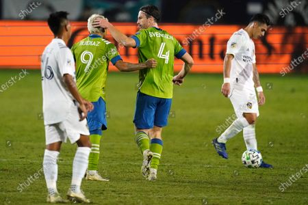 Seattle Sounders forward Raul Ruidiaz, second from left, celebrates with midfielder Gustav Svensson after Ruidiaz scored a goal against the LA Galaxy during the second half of an MLS soccer match, in Carson, Calif. The Sounders tied LA Galaxy 1-1