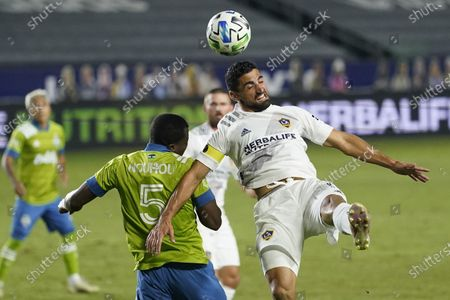Galaxy midfielder Sebastian Lletget, right, heads the ball next to Seattle Sounders defender Nouhou Tolo during the first half of an MLS soccer match, in Carson, Calif