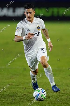 Stock Photo of Galaxy forward Cristian Pavon runs with the ball during the first half of an MLS soccer match, in Carson, Calif