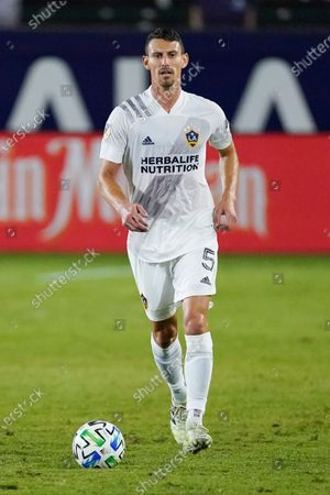 Galaxy defender Daniel Steres runs with the ball during the first half of an MLS soccer match, in Carson, Calif