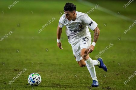 Galaxy forward Cristian Pavon runs with the ball during the first half of an MLS soccer match, in Carson, Calif