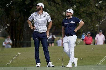 Tyrrell Hatton and Dustin Johnson stand on the 11th green during the first round of the Houston Open golf tournament, in Houston