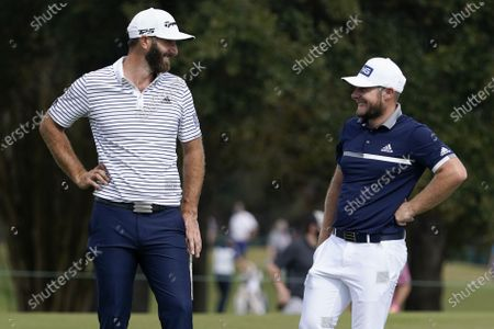Tyrrell Hatton and Dustin Johnson talk on the 11th green during the first round of the Houston Open golf tournament, in Houston