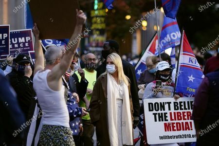 Former Florida Attorney General Pam Bondi, center, wears a protective mask while standing with supporters of President Donald Trump's campaign outside the Pennsylvania Convention Center where votes are being counted, in Philadelphia, following Tuesday's election