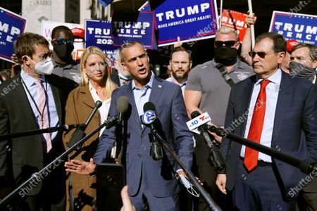 President Donald Trump's campaign advisor Corey Lewandowski, center, speaks outside the Pennsylvania Convention Center where votes are being counted, in Philadelphia, following Tuesday's election. At left is former Florida Attorney General Pam Bondi