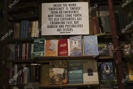 "Panel on ""Emergency"" by Rebecca Solnit hangs on the book shelves of the English and American literature Shakespeare and Co. bookstore, in Paris, France, . Iconic Parisian bookshop Shakespeare and Co. has launched a support appeal to its readers after its owners say that coronavirus-linked losses, and a crippling months-long lockdown, have left the future of the veritable institution in doubt. ""We've been minus 80 percent since the first confinement in March, so at this point we've used all our savings,"" Sylvia Whitman, daughter of the shop's co-founder George Whitman, told the Associated Press"