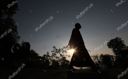 A Buddhist monk as he walks near the Tibetan's main temple of Tsuglagkhang, popularly known as the Dalai Lama temple, during sunset in McLeod Ganj, Himachal Pradesh, India, 05 November 2020.