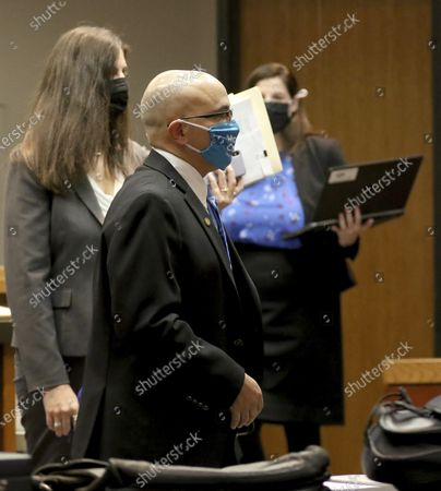 Former DCFS caseworker and current McHenry County board member Carlos Acosta, center, leaves court with attorney Rebecca Lee, left, inside Judge Robert Wilbrandt's courtroom on at the Michael J. Sullivan Judicial Center, in Woodstock, Ill. Acosta was the caseworker assigned to the AJ Freund case