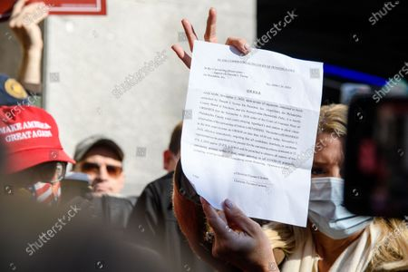 Stock Photo of Former Florida Attorney General Pam Bondi shows reporters a court order granting President Donald Trump's campaign more access to vote counting operations at the Pennsylvania Convention Center, Thursday, Nov. 5, 2020, in Philadelphia, PA.