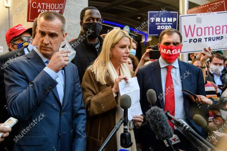 Former Florida Attorney General Pam Bondi, center, shows reporters a court order granting President Donald Trump's campaign more access to vote counting operations at the Pennsylvania Convention Center, Thursday, Nov. 5, 2020, in Philadelphia, PA.