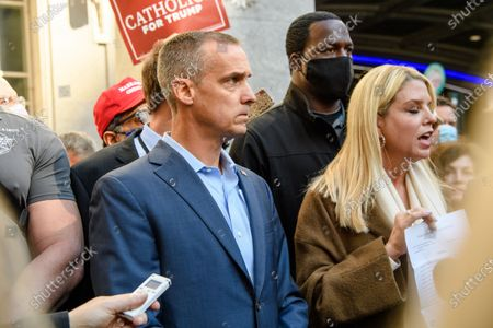 Trump campaign advisor Corey Lewandowski, left, stands by as Former Florida Attorney General Pam Bondi shows reporters a court order granting President Donald Trump's campaign more access to vote counting operations at the Pennsylvania Convention Center, Thursday, Nov. 5, 2020, in Philadelphia, PA.