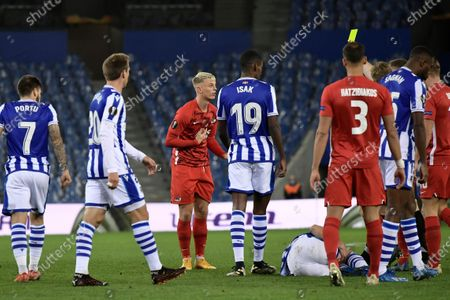 Alkmaar's Albert Gudmundsson, centre left, is shown a yellow card by the referee during the Europa League Group F soccer match between Real Sociedad and AZ Alkmaar at the Anoeta stadium in San Sebastian, Spain