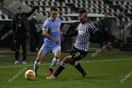 PSV's Ryan Thomas, left, passes the ball as PAOK's Dimitris Giannoulis tries to stop him during the Europa League group E soccer match between PAOK and PSV Eindhoven at Toumba stadium in the northern city of Thessaloniki, Greece