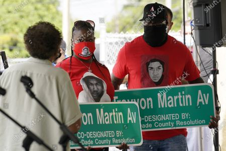 Stock Picture of Sybrina Fulton, center and Tracy Martin, parents of Trayvon Martin, hold street signs with their son's name, in Miami Gardens, Fla. The street on the way to Martin's former school was renamed in his honor, eight years after he was killed by a neighborhood watch volunteer in Sanford, Fla