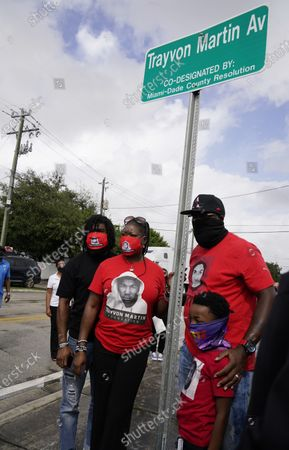Stock Photo of Sybrina Fulton, and Tracy Martin, parents of Trayvon Martin, together with Jahvaris and Tyler Martin, stand next to a sign at the renaming of a street in honor of their son, in Miami Gardens, Fla. Trayvon Martin was killed by a neighborhood watch volunteer in Sanford, Fla., in 2012