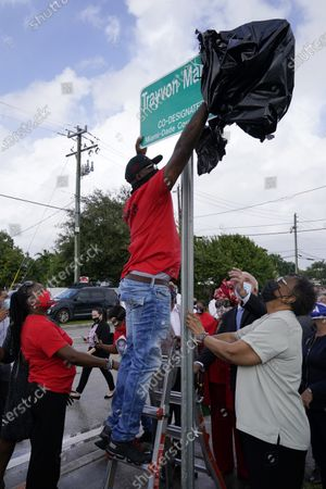 Tracy Martin, father of Trayvon Martin, unveils a sign renaming a street in honor of his son, in Miami Gardens, Fla. To the left is Sybrina Fulton, Trayvon's mother. Trayvon Martin, 17, was killed by a neighborhood watch volunteer in Sanford, Fla., in 2012