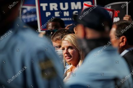 Former Florida Attorney General Pam Bondi, framed between police officers, speaks outside the Pennsylvania Convention Center in Philadelphia, as vote counting in the general election continues