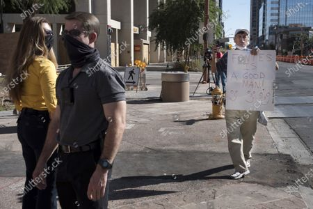 Demonstrating outside Phoenix City Hall, a counter-protestor shows support for Maricopa County Recorder Adrian Fontes, shouting at and video taping a group of about 100 supporters of President Donald J. Trump who suggest that officials are trying to steal the vote as counting continues at the nearby Recorder's office Phoenix, Arizona, USA, 05 November 2020. Plainclothes police, at left keep the people separated. The 2020 Presidential Election result remains undetermined as votes continued to be counted in several key battleground states.