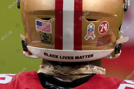 San Francisco 49ers running back Jerick McKinnon wears a logo for Salute to Service, the words Black Lives Matter and a 74 for former player Fred Dean before an NFL football game against the Green Bay Packers in Santa Clara, Calif